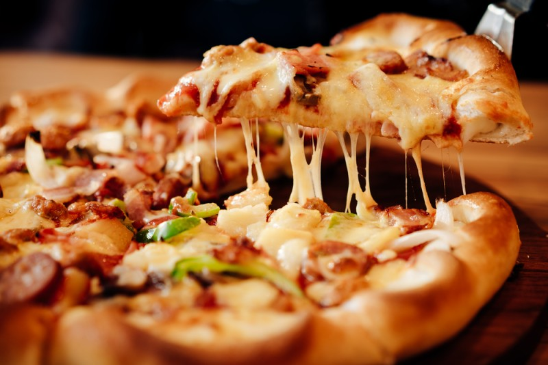 a close-up of a hot, cheesy pizza on a wooden board