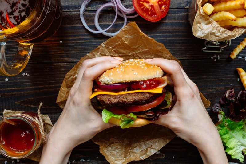 top view of hands holding fresh mouthwatering burgers with fries, beer and sauce on the wooden table.